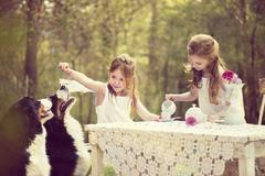 Two girls having a tea party in the garden with two dogs - stock photo
