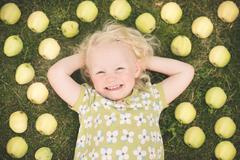 Elevated view of a girl lying on the grass surrounded by apples Stock Photos