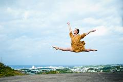 Ballerina leaping in the air on a roof, Okinawa, Japan - stock photo