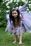 Girl wearing a tutu dress playing in the rose garden - stock photo