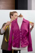Mid adult woman measuring shirt on mannequin - stock photo