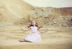 Girl sitting in the desert with her arms outstretched Stock Photos