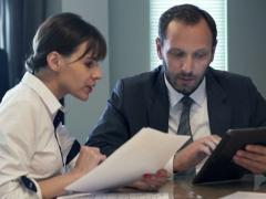 Stock Video Footage of businesspeople comparing data on tablet and documents by table in theoffice NTSC