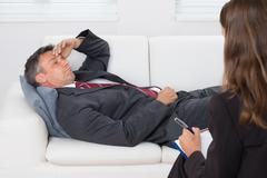 Patient Relaxing On Couch In Front Of A Female Psychiatrist With Clipboard Stock Photos