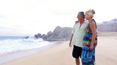 An older couple looking out at the ocean when the waves sneak up on them - stock footage