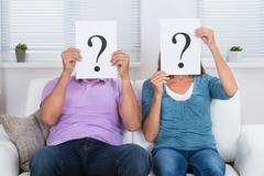 Couple Together Sitting On Sofa Hiding Face With Question Mark Sign - stock photo