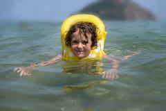 Smiling girl wearing a rubber life jacket in the sea, Thassos, Greece Stock Photos