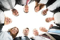 Directly below portrait of confident business team standing in huddle against - stock photo