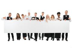 Portrait of confident restaurant staff holding blank billboard against white  - stock photo
