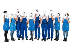 Full length of janitors hiding faces with question mark signs against white b - stock photo