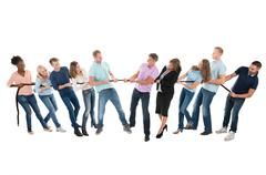 Full length of multiethnic creative business teams playing tug of war against - stock photo