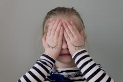 Girl covering her eyes with hands that have eyes drawn on them Stock Photos