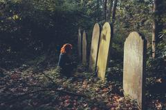 Grieving woman by grave - stock photo