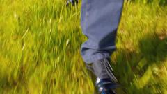 A man walks through the grass. Shoes closeup Stock Footage