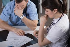Surgeons analysing patient clinical documentation - stock photo