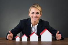 Portrait of happy businesswoman with model houses arranged in graph order Stock Photos
