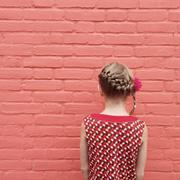 Rear view of a girl with a plait and a flower in her hair - stock photo