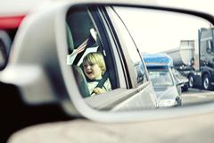 Reflection in a car wing mirror of a boy sitting in a car Kuvituskuvat