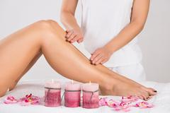 Midsection of beautician waxing woman's leg at salon - stock photo