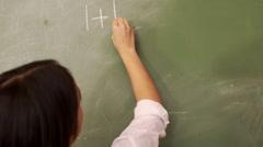 Teacher writing on blackboard - stock footage