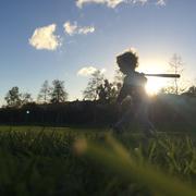 Boy playing with baseball bat - stock photo