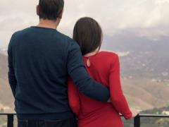 Young couple hugging and admire mountain view from the terrace NTSC Stock Footage