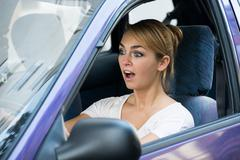 Shocked young woman with mouth open driving car Stock Photos