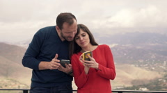 Young couple talking over smartphones on terrace with mountain view HD Stock Footage