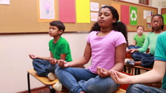 Pupils doing yoga in classroom Stock Footage