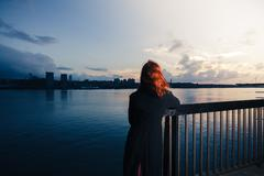 Woman admiring sunset over river in city Stock Photos