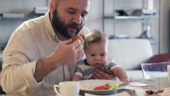 Young father eating breakfast with small son on his knee HD Stock Footage