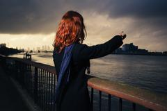Woman admiring sunet over river in city - stock photo