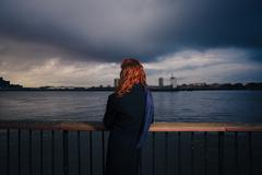 Woman admiring sunet over river in city Stock Photos