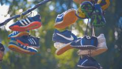 Related laces sneakers hanging on wires and swaying in the wind - stock footage