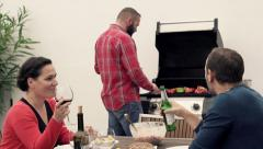 Young friends talking and drinking alcohol during grill party at terrace HD Stock Footage