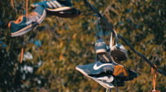 Related laces sneakers hanging on wires and swaying in the wind Stock Footage