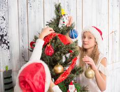 Teenage girls decorating New Year tree at home Stock Photos