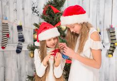 Stock Photo of Teenage girls decorating New Year tree at home