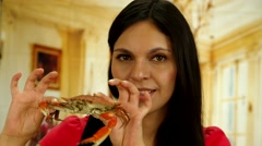 Attractive brunette holding crab up and smiling to camera Stock Footage