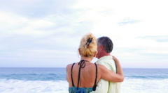 Close up of an older couple at the beach with their arms around each other - stock footage