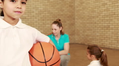 Smiling girl with thumbs up holding basketball Stock Footage