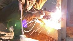 Worker in protective mask welding steel railings outdoors Stock Footage