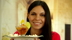 Attractive brunette holding plate with shrimp cocktail and smiling Stock Footage
