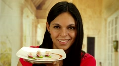 Brunette holding up plate with delicious pieces of fish and smiling to camera Stock Footage