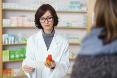Pharmacist Reading the Prescription at the Counter Stock Photos