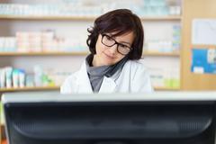 Pharmacist Talking on Phone While Checking Stocks Stock Photos