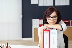 Office Woman Leaning on Binders on the Table - stock photo
