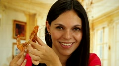 Attractive brunette holding a big prawn and smiling to camera Stock Footage