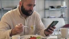 Young man with smartphone eating breakfast in the morning HD Stock Footage