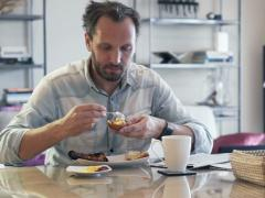 Young man spreading jam during breakfast by dinning table at home PAL - stock footage